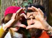 Couple In Love Shows Heart Sign With Fingers. poster