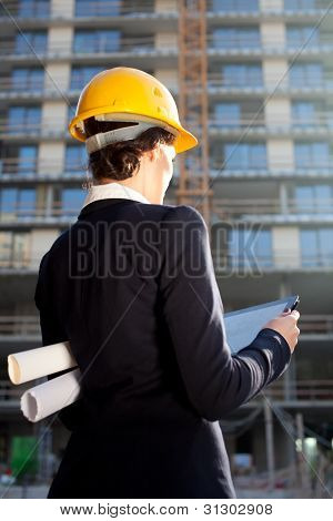 Female Architect/construction Engineer Reviewing Plans At Construction Site