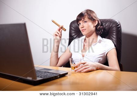 Young Businesswoman Smoking A Cigar And Drinking Whiskey