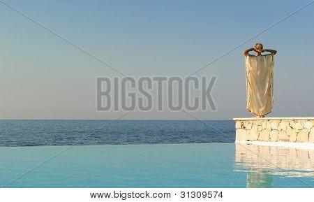 Rear View Of Greek Style Woman Near Infinity Pool