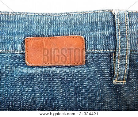 blank leather label sewed on blue jeans