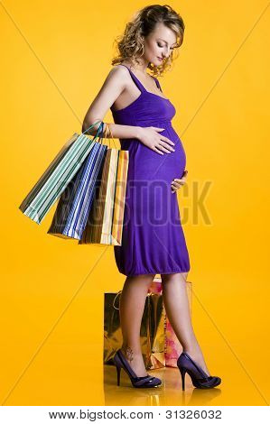 Lovely Pregnant Woman Holding Shopping Bags Over Yellow Background
