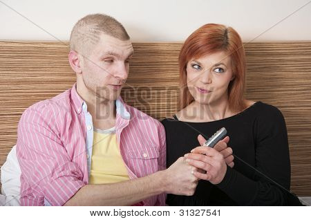 couple arguing fighting over TV remote control