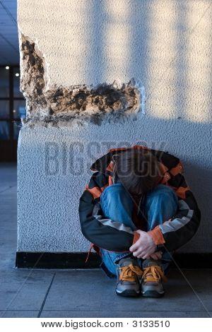 Boy Teens Sitting On The Floor Alone In City (Series Teenagers)