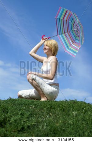 Young Charming Girl Sitting On The Meadow With Umbrella