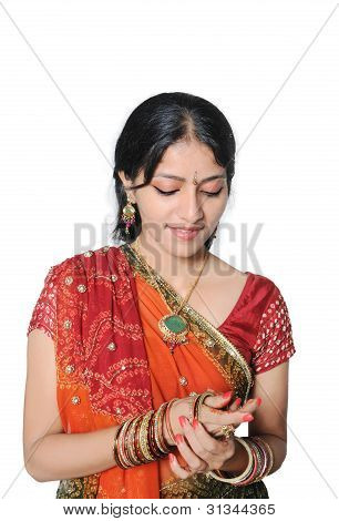 Traditional Indian Girl wearing bangles in her hand.