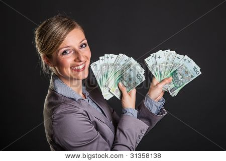Woman with polish zloty money on dark gray background