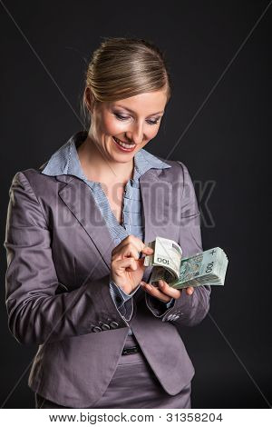 Woman with polish zloty money on dark gray background
