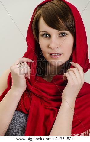 Young Woman In A Red Scarf. On Grey Background.