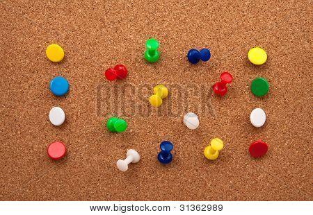 Colorfull Thumbtacks in cork bulletin board