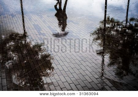 Couple with umbrella walking in reflection