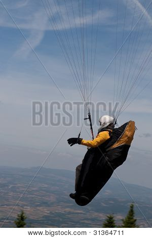Paraglider over the mountains against light cloudy blue sky