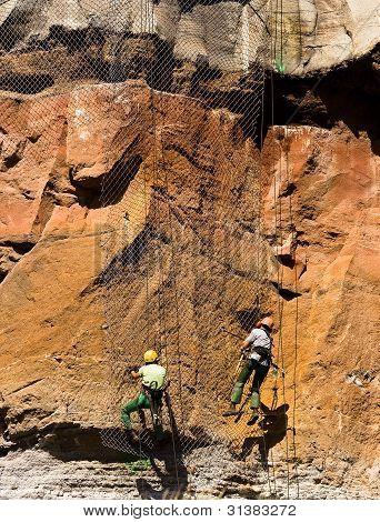Workers tension a metallic net