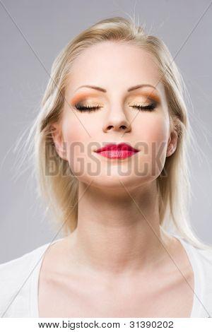 Young Blond Woman Displaying Elegant Makeup.