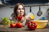 Young Cheerful Girl Prepares A Vegetarian Salad In The Kitchen, She Chooses Red Or Yellow Pepper, Th poster