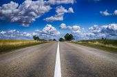 Low Angle View Of A Tarred Road Receding Into The Distance In Open Countryside Under A Cloudy Blue S poster