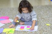 Cute Little Girl Make Applique, Glues Colorful House, Applying A Color Paper Using Glue Stick While  poster