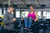 Side view of Caucasian Male trainer assisting young Caucasian female athlete with exercise in fitnes poster