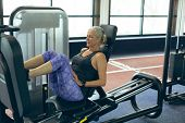 Side view of active senior Caucasian woman exercising with leg press machine in fitness studio. Brig poster