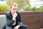 Cheerful Pensive Office Employee Posing Outdoors. Young Business Man In Eyeglasses And Jacket Sittin poster