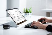 Businessperson Analyzing Invoice On Laptop poster