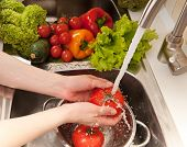 stock photo of mixing faucet  - Fresh vegetables splashing in water before cooking - JPG