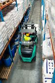 High angle rear view of African-american male worker driving forklift in warehouse. This is a freigh poster
