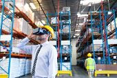 Front view of handsome Caucasian male supervisor using virtual reality headset in warehouse. This is poster