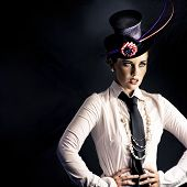 image of vaudeville  - An actress dressed in typical vaudeville costume with a fascinator hat and tie performing on a darkened stage facing out of frame to an unseen audience - JPG