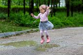 Little Girl In Rubber Boots And Tutu Dress Jumping In Puddle. Water Is Splashing From Kid Feet As Sh poster