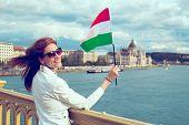 Happy Young Redhead Hungarian Urban Woman Waving Hungarian Flag At Budapest poster