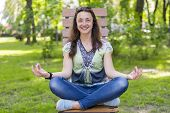 Young Woman Doing Yoga In The Park On The Bench. Portrait Of Calm Beautiful Young Brunette Woman Rel poster