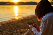 Young Millennial Girl Sitting On The Sandy Shore At Sunset And Looking At The Screen Of Her Smartpho poster