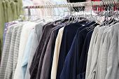 Fashionable Clothing On Hangers In Shop. Sport Of T Shirts Are Hanging On Clothes Hanger , T Shirt.  poster