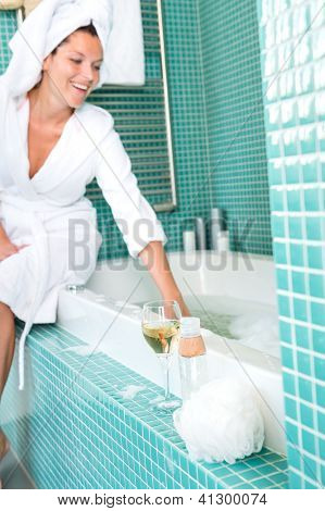 Smiling woman relaxing wrapped towel bathroom bathtub playing foam