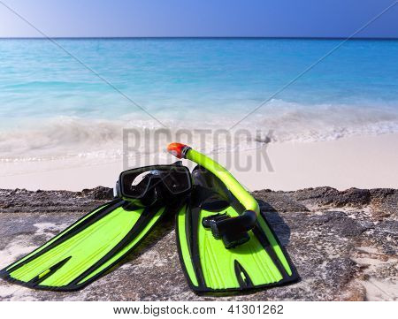 mask flippers tube-lay on sand on background of ocean