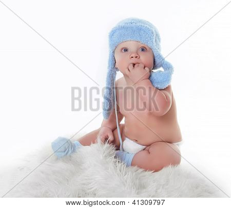 Cute Little Baby Is Looking And Wearing Blue Hat Over White