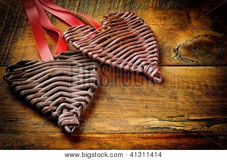 Two Wicker Hearts On  Wooden Table