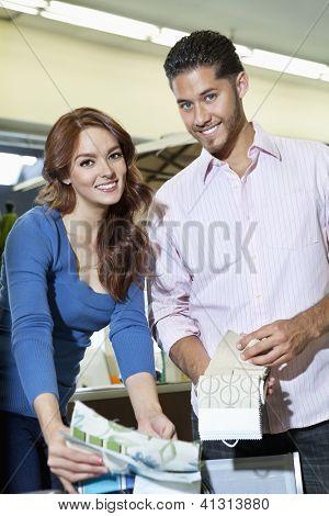 Retrato de la joven pareja con muestras de textiles en tienda