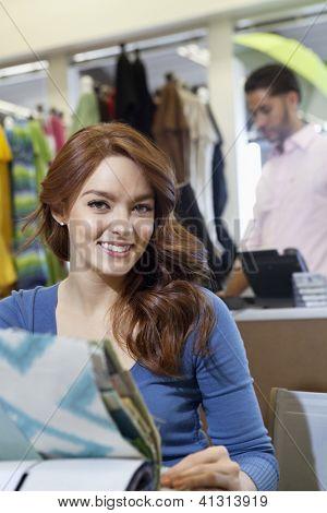 Retrato de mujer joven hermosa con muestras de textiles al hombre en el fondo
