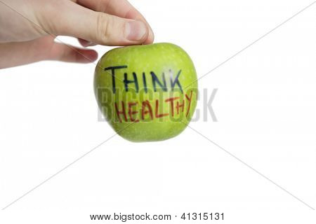 Soft focus of a cropped image of hand holding healthy granny smith apple over white background