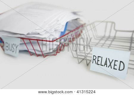 Stack of paperwork in busy tray with empty relaxed platter over white background