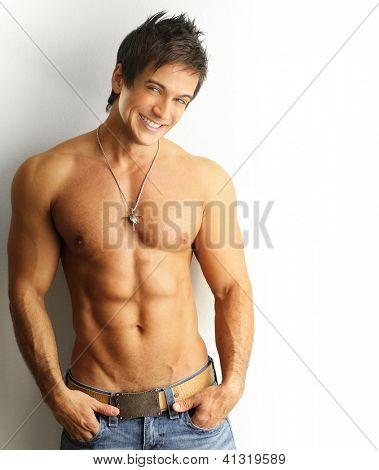 Sexy Portrait eines jungen muskulösen männlichen Modells mit großen glücklichen Lächeln gegen weiße Wand