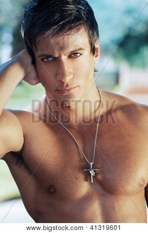 Close-up portrait of handsome shirtless man outdoors