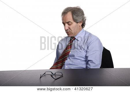 sad  mature business man on a desk, isolated on white