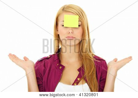 A portrait of a young confused woman with a sticky note on her forehead