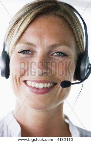 Businesswoman In Office Wearing Headset And Smiling
