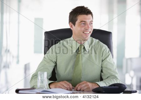 Empresario sentado en la oficina con Organizador Personal sonriente