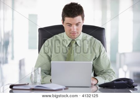 Businessman Sitting In Office With Personal Organizer And Laptop