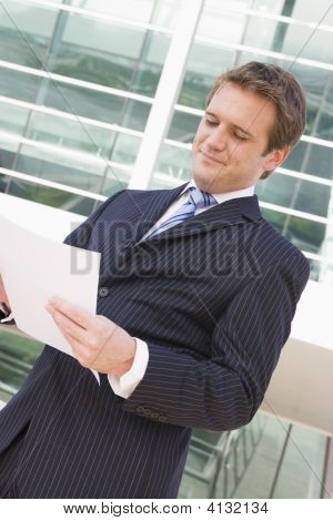 Businessman Standing Outdoors Looking At Paperwork